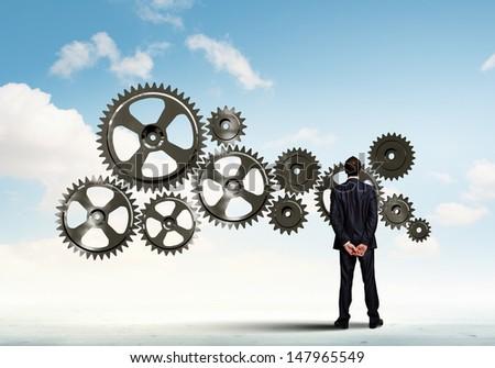 Businessman with cog wheel elements. Construction concept - stock photo