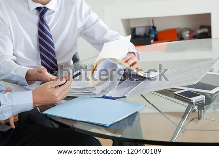 Businessman with colleague discussing paperwork at desk in office - stock photo