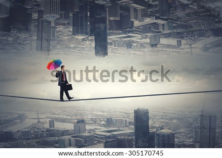 Businessman with colorful umbrella and suitcase walking on rope - stock photo