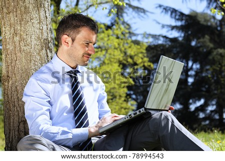 businessman with computer in a park in summer - stock photo