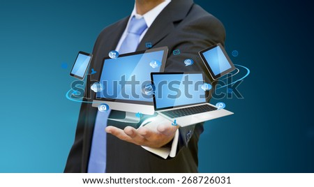Businessman with computer phone and tablet in his hand - stock photo