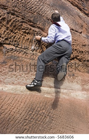 Businessman with cravat climbing a rock - stock photo