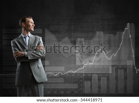 Businessman with crossed arms and growing graphs on chalkboard