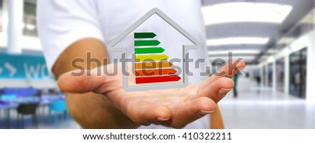 Businessman with 3D eco house and energy efficiency in his hand - stock photo
