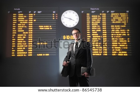 Businessman with departures and arrivals board of a train station in the background - stock photo