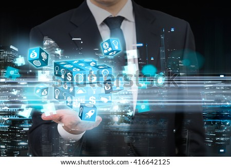 Businessman with digital cube puzzle on night city background - stock photo