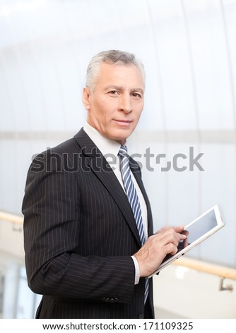 Businessman with digital tablet. Confident senior man in formalwear holding a digital tablet and looking at camera - stock photo