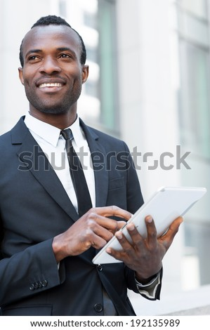 Businessman with digital tablet. Confident young African man in formal wear working on digital tablet and looking away with smile while standing outdoors - stock photo