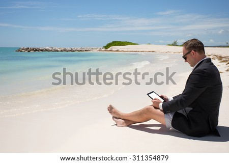 Businessman with digital tablet on the beach - stock photo