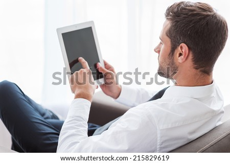 Businessman with digital tablet. Rear view of confident young businessman in shirt and tie working on digital tablet while sitting at the chair - stock photo