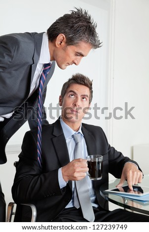 Businessman with digital tablet showing something to colleague at desk in office - stock photo