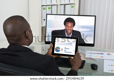 Businessman With Digital Tablet Video Chatting With Male Colleague On Computer In Office - stock photo