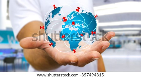 Businessman with digital world map and pins floating over his hand - stock photo