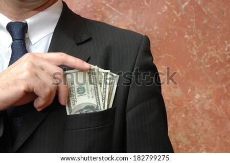 Businessman with dollars bills in the pocket, concept of corruption - stock photo