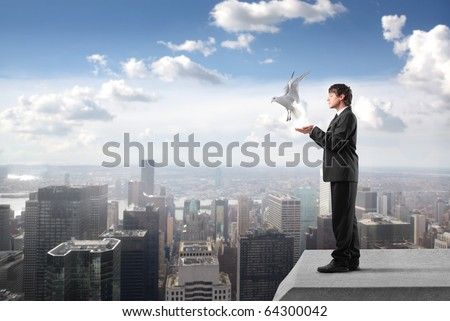 Businessman with dove flying from his hands on the rooftop of a skyscraper - stock photo