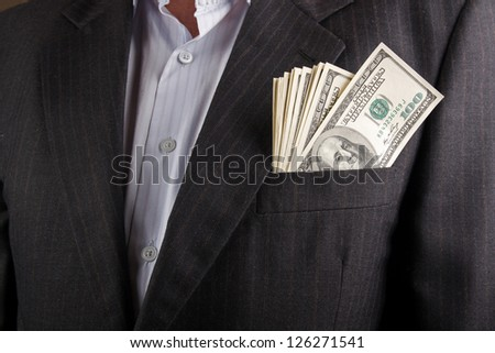 businessman with earned money in suit pocket - stock photo