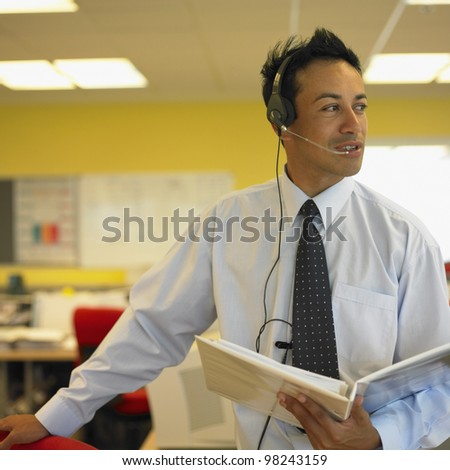 Businessman with earpiece holding notebook - stock photo