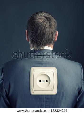 Businessman with electrical outlet on back - stock photo