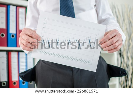 Businessman with empty pockets showing graphs with poor results - stock photo