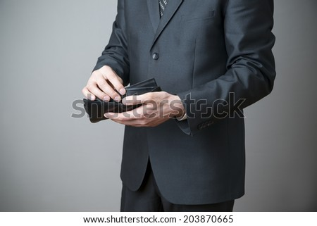 Businessman with empty purse in hands on a gray background - stock photo