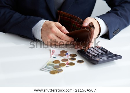 Businessman with empty wallet and a few coins on the table - stock photo