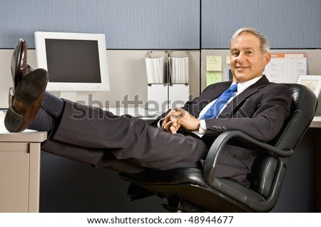 Businessman with feet up at desk - stock photo