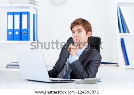 businessman with finger on lips smile sitting at the desk in office, handsome young business man, concept of silence, commercial financial secret - stock photo