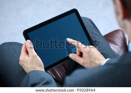 Businessman with finger touching screen of a digital tablet whilst sitting on a sofa