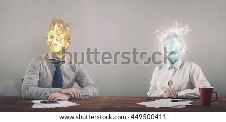 Businessman with fire head and businesswoman with water instead of her head sitting in office. - stock photo
