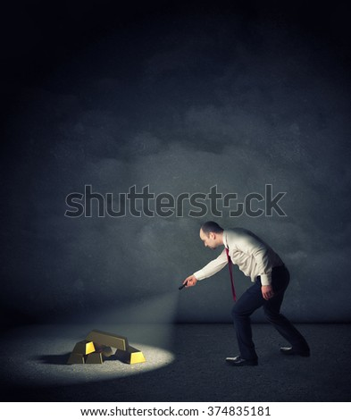 businessman with flashlight find gold ingot