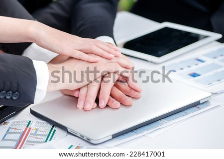 Businessman with folded hands on the laptop. Four smiling successful businessmen sitting at table in office while discussing their business doings. Young people talking in office