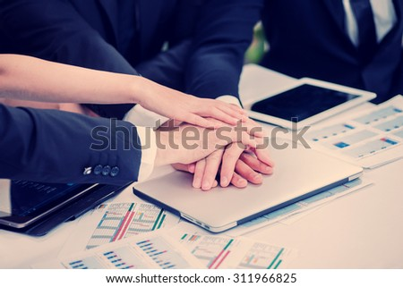 Businessman with folded hands on the laptop. Four smiling successful businessmen sitting at table in office while discussing their business doings. Young people talking in office - stock photo