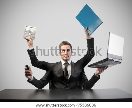 Businessman with four arms holding various instruments for communication - stock photo