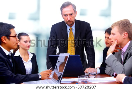 Businessman with four businesspeople at boardroom table in background - stock photo