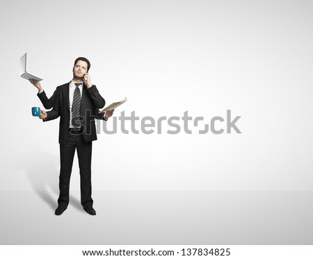 businessman with four hands holding various instruments on white background