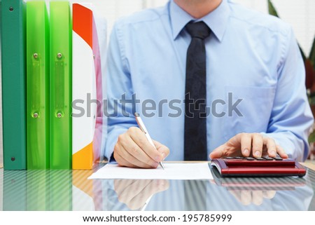 businessman with full of paperwork is completing form - stock photo