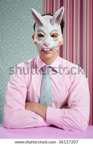 Businessman with funny rabbit easter mask portrait over wallpaper - stock photo