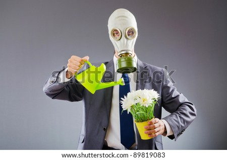 Businessman with gas mask and flowers - stock photo