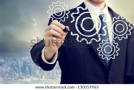 Businessman with gears - concepts of teamwork, efficiency, interlocking parts. - stock photo