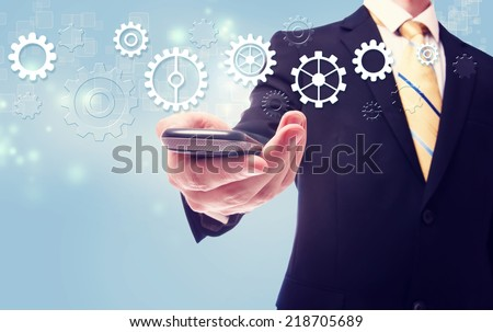 Businessman with gears over a cellphone on light blue background - stock photo