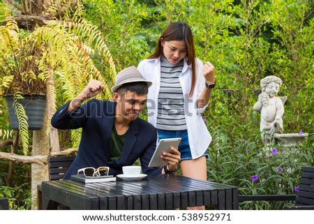 Businessman with girl reading the paper reported in a coffee shop.