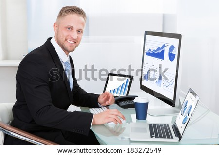 Businessman with good performance graph sitting at his desk with statistical reports spread over three monitors cheering and clasping his fists - stock photo