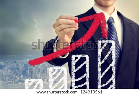 Businessman with graph representing growth above the city - stock photo