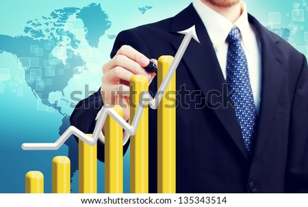 Businessman with graph representing growth with world map backdrop