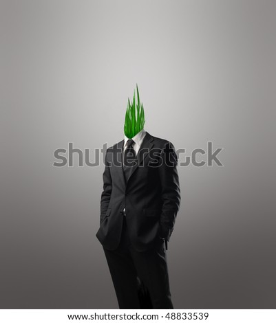 Businessman with grass instead of his head - stock photo