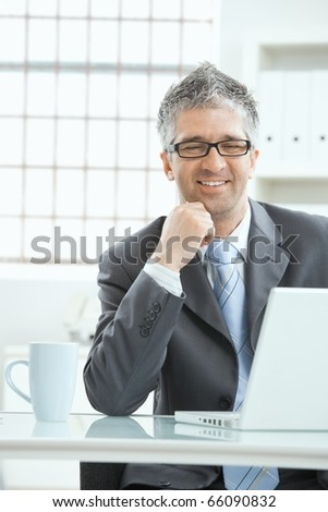 Businessman with gray heair thinking over laptop computer, sitting at desk, smiling.?