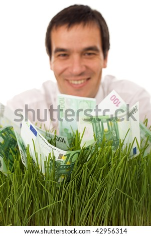 Businessman with green banknotes in grass - environmental friendly business concept, focus on money, isolated - stock photo