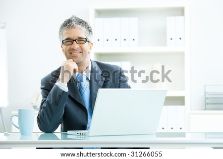 Businessman with grey hair, wearing grey suit and glasses thinking over laptop computer, sitting at desk in bright, modern office, leaning on hand, smiling.