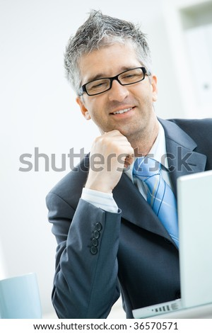 Businessman with grey hair, wearing grey suit and glasses thinking over laptop computer, sitting at office desk leaning on hand.