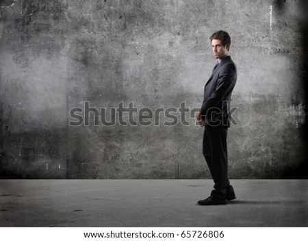 Businessman with grey wall on the background - stock photo